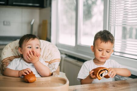 Foto de charming children in the kitchen in the afternoon eating buns with poppy seeds, boy and girl, family - Imagen libre de derechos