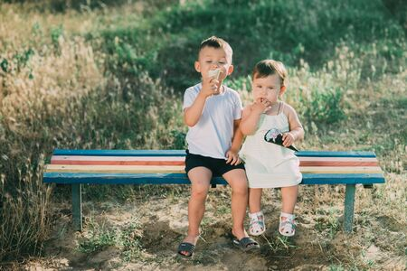 Foto de Brother and sister eating ice cream on the bench in the Playground - Imagen libre de derechos