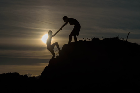 Foto de Silhouette of two boys helped pull together climbing - Imagen libre de derechos