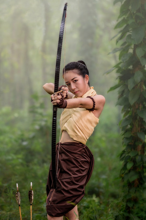 Photo for Beautiful ancient archery woman with bow and arrows aiming in forest background - Royalty Free Image