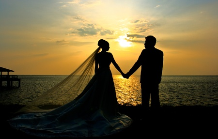 Romantic silhouette of wedding couple at sunset
