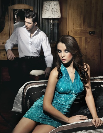 Handsome young couple resting in bedroom before night party