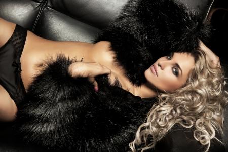 Photo pour Beauty blond woman posing on black sofa - image libre de droit