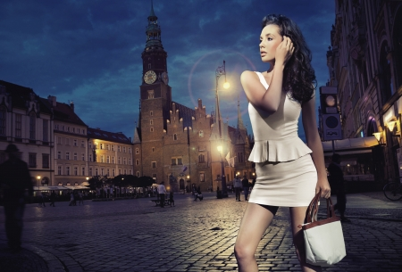 Photo pour Sexy young beauty posing over night city background - image libre de droit