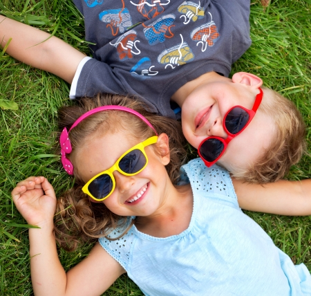 Photo pour Picture presenting kids relaxinng on the green grass - image libre de droit