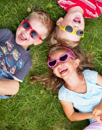 Photo pour Laughing children relaxing during summer day - image libre de droit