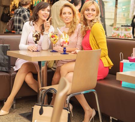 Foto de Relaxed women eating tasty fruit ice cream - Imagen libre de derechos