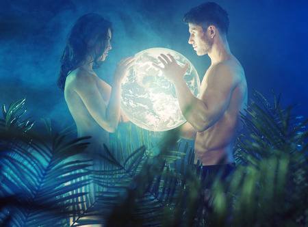 Foto de shirtless young couple holding shiny Earth - Imagen libre de derechos