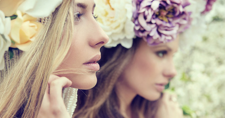 Photo for Portrait of the two gorgeous ladies with wild flowers - Royalty Free Image