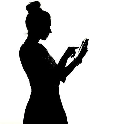 Photo pour Silhouette of a lady uisng the smartphone - image libre de droit