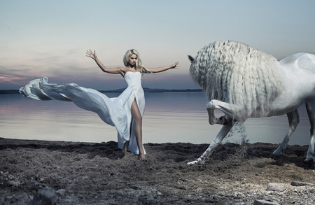 Photo for Alluring woman taming the white horse - Royalty Free Image