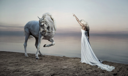 Photo pour Shapely woman standing opposite the white horse - image libre de droit