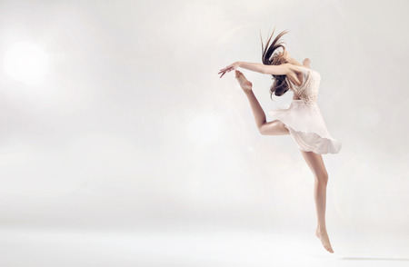 Foto de Pretty female ballet dancer in hard jump figure - Imagen libre de derechos