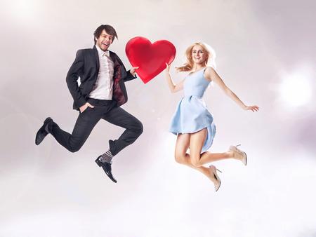 Photo pour Fine photo of cheerful couple holding a cartoon heart - image libre de droit