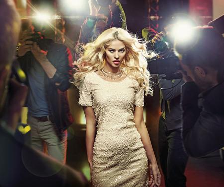 Photo pour Young blond star among the nosy paparazzi - image libre de droit