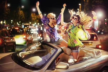 Foto de Two joyful women dancing in the cabriolet - Imagen libre de derechos