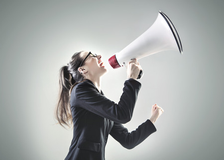 Photo pour Portrait of a pretty businesswoman yelling over the megaphone - image libre de droit