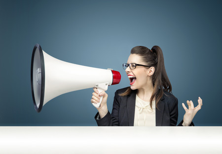 Foto de Young pretty businesswoman yelling over megaphone - Imagen libre de derechos