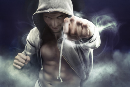 Foto de Hooded muscular boxer punching an enemy - Imagen libre de derechos