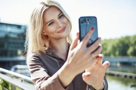 Foto de Portrait of a blond lady taking a selfie - Imagen libre de derechos