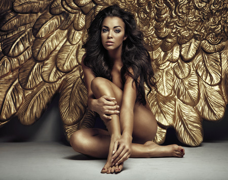 Photo for Portrait of a sexy angel with gold wings - Royalty Free Image