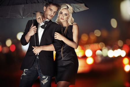 Photo pour Smart couple walking with the black umbrella - image libre de droit