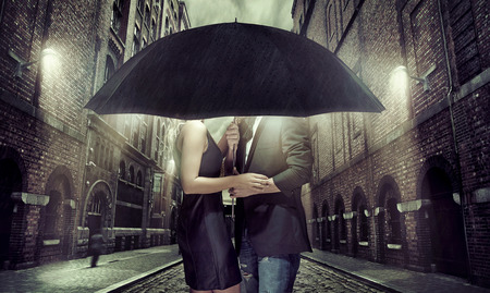 Cheerful couple hiding themselves under the umbrella
