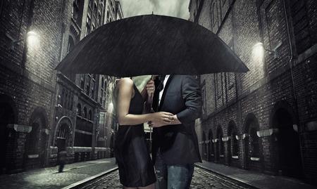 Adorable couple under the black umbrella