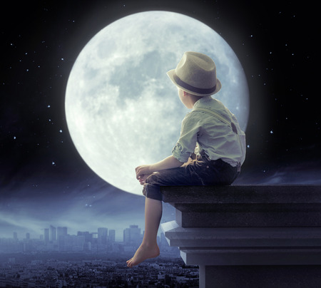 Photo pour Little boy looking a the city in the night - image libre de droit