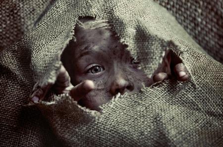 Foto de Portrait of a poor dirty boy kid - Imagen libre de derechos