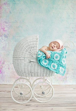 Photo pour Cute child sleeping in the wicker pram - image libre de droit
