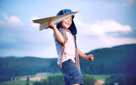Foto de Cheerful little boy toy paper plane - Imagen libre de derechos