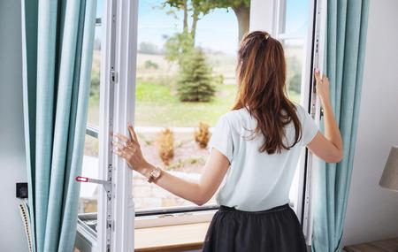 Photo pour Elegant woman opening the bedroom window - image libre de droit