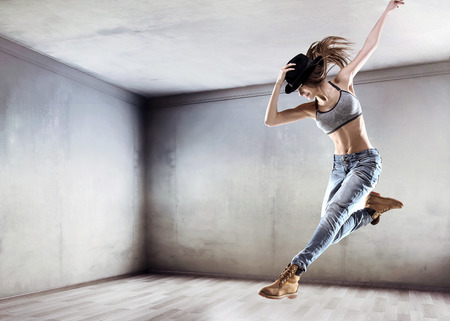 Photo pour Athletic young dancer jumping on a concrete wall background - image libre de droit