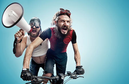 Photo pour Two hilarious bicyclists involved in a contest - image libre de droit