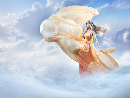 Foto de Dreamy image of a beautiful young woman in the clouds - Imagen libre de derechos
