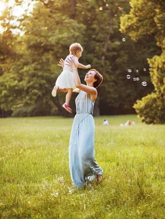 Foto de Delighted young mother tossing her lovely child - Imagen libre de derechos