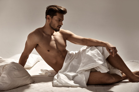 Photo for Handsome, muscular guy posing on the soft bed - Royalty Free Image