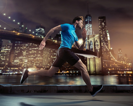 Foto de Handsome young jogger running through the city in the night - Imagen libre de derechos