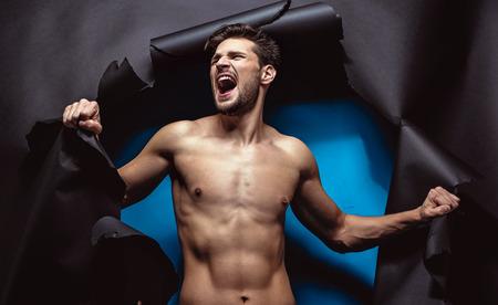 Foto de Furious young man tearing up the black background - Imagen libre de derechos