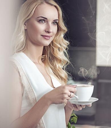 Photo pour Portrait of a pretty blond lady drinking a cup of coffee - image libre de droit