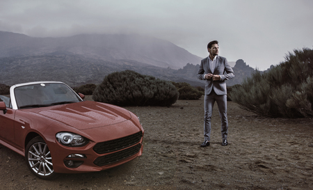 Photo for Young businessman standing next to the luxurious convertible - Royalty Free Image
