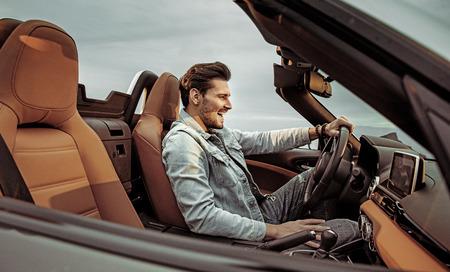 Photo pour Handsome, young man riding a luxuriois convertible - image libre de droit