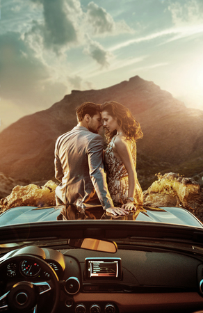 Photo for Romantic, young couple sitting on the bonnet - Royalty Free Image