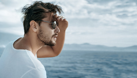 Photo pour Portrait of a handsome guy watching ocean waves - image libre de droit