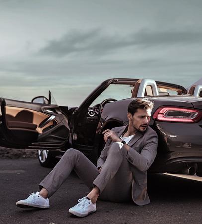 Photo pour Elegant guy leaning on the luxurious car - image libre de droit