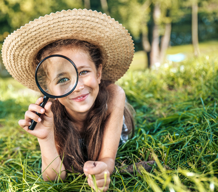 Photo pour Pretty girl holding a magnifying glass - image libre de droit