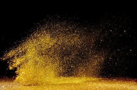 Photo pour Golden, shining powder scattered over the dark background - image libre de droit