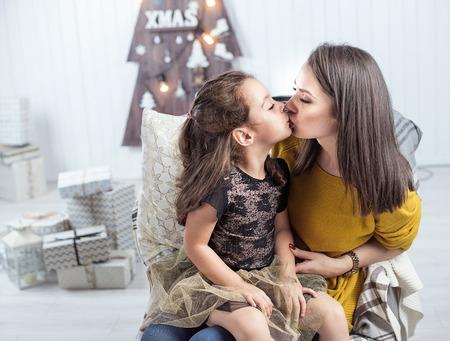 Photo pour Portrait of a pretty mother kissing a daughter - image libre de droit