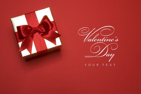 Photo for golden gift box with a red bow on red background - Royalty Free Image